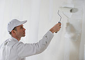 Male painter painting with paint roller