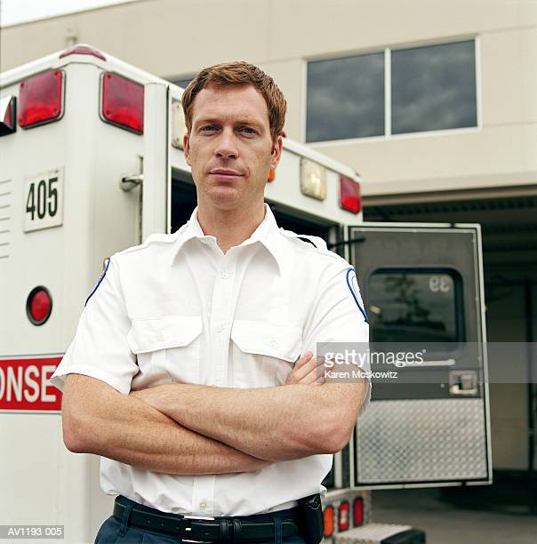 Male paramedic standing at rear of ambulance, arms folded, portrait