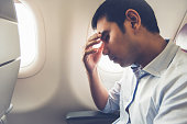 Male passenger feeling dizzy having airsickness while traveling on the plane