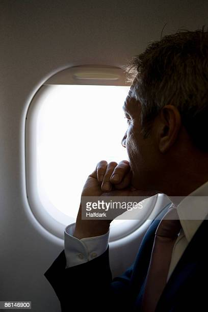 A male passenger looking through a window on a plane