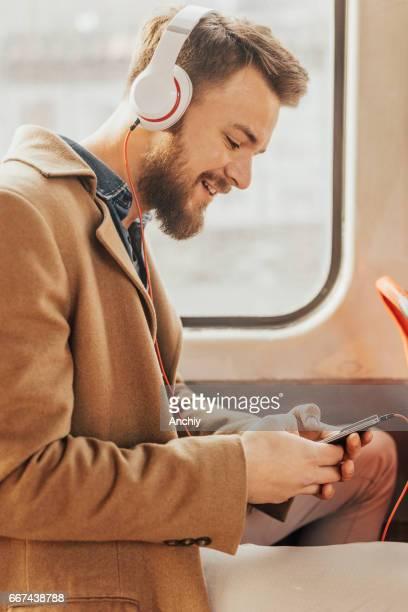 männlichen Passagier auf ein öffentliches Verkehrsmittel, das Anhören von Musik auf seinem smartphone