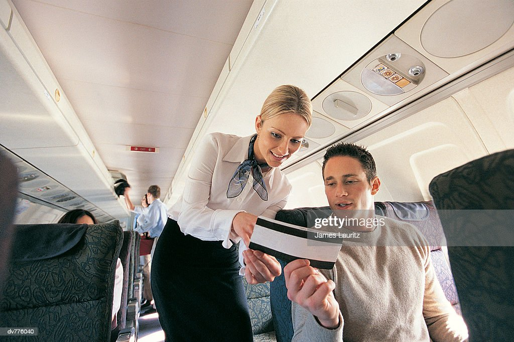 Male Passenger Showing His Ticket to an Air Stewardess on an Aeroplane