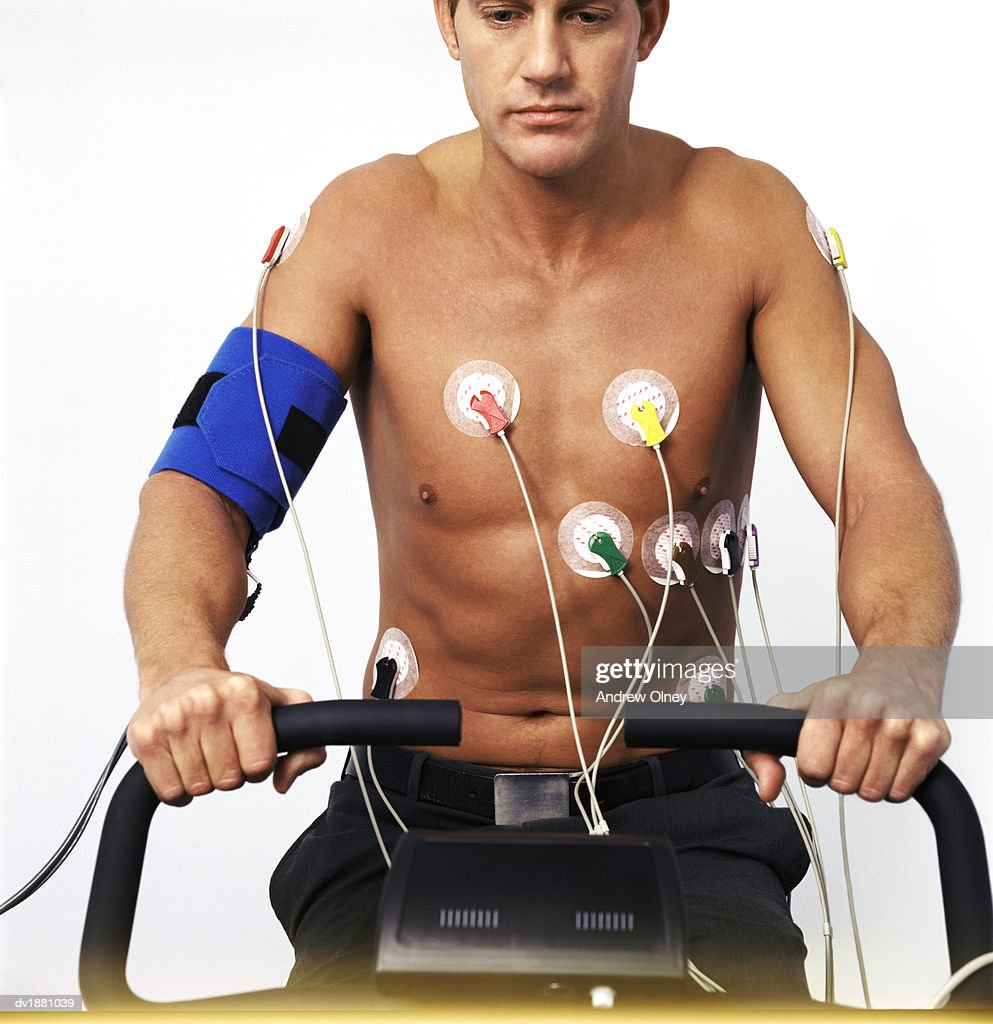 Male Patient Exercising While Connected to Heart Rate Monitoring Equipment : Stock Photo
