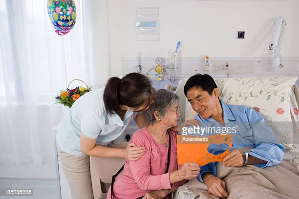 Male patient holding a Get Well card with his family
