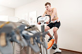 A male patient, pedaling on a bicycle ergometer stress test system for the function of his heart checked. Athlete does a cardiac stress test in a medical study, monitored by the doctor. Athlete Perfor