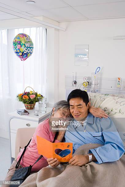 Male patient reading a Get Well card beside his mother