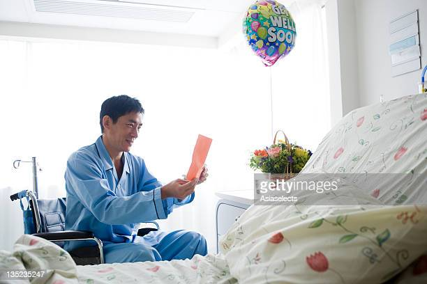 Male patient sitting in a wheelchair and reading a Get Well card