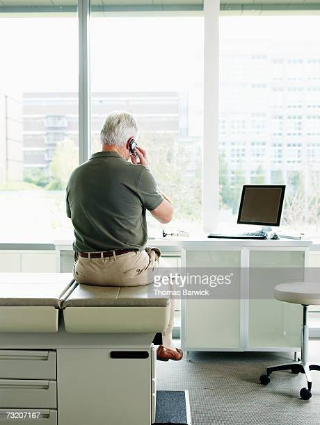Male patient sitting on exam table in exam room, talking on mobile phone, rear view