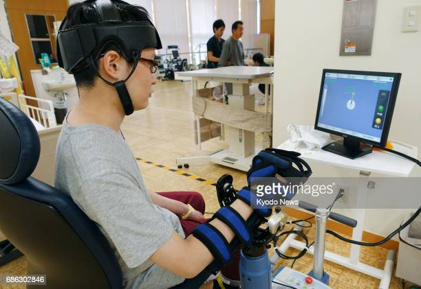 A male patient uses a robotic arm sold by Teijin Pharma Ltd at Kansai Rehabilitation Hospital in Toyonaka Osaka Prefecture on Jan 30 2017 The...