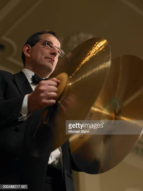 Male percussionist playing cymbals in orchestra, low angle view