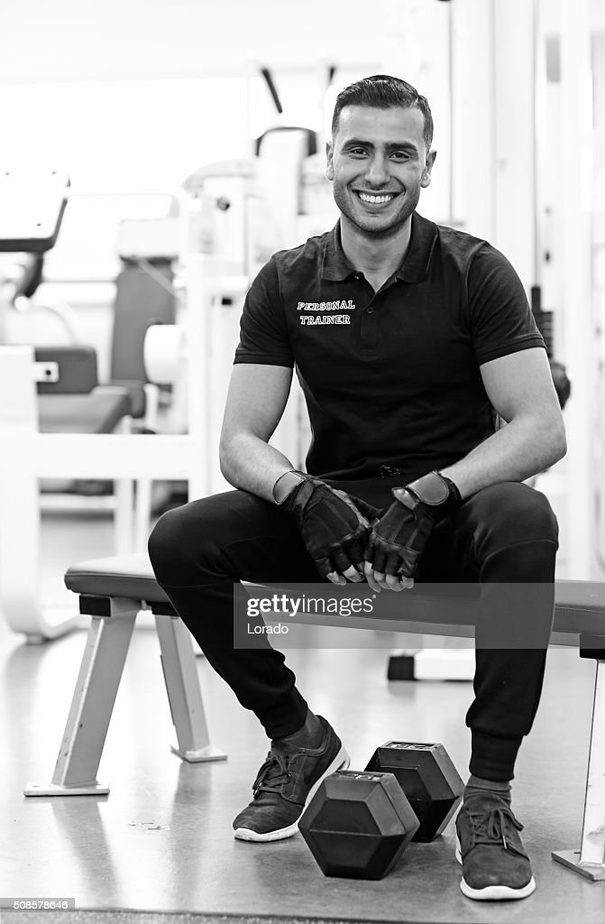 male personal trainer posing in gym : Stock Photo