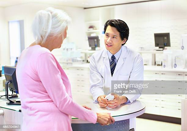 Male pharmacist advising customer on medication