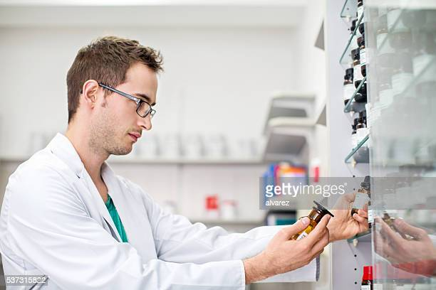 Male pharmacist examining medicine bottle