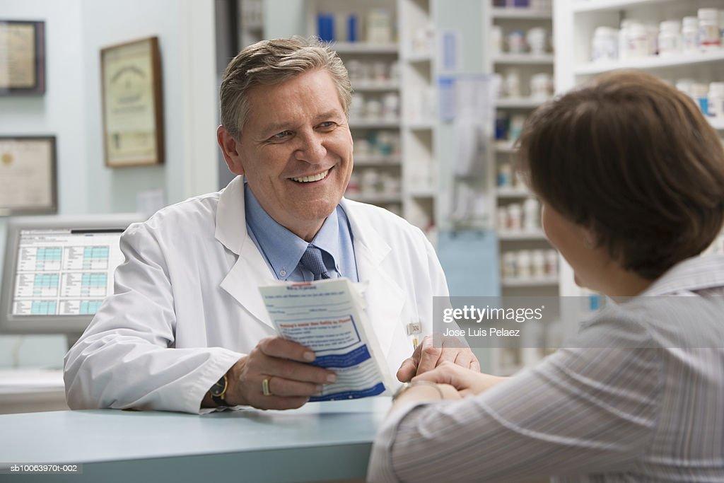 Male pharmacist giving prescription to woman : Stock Photo