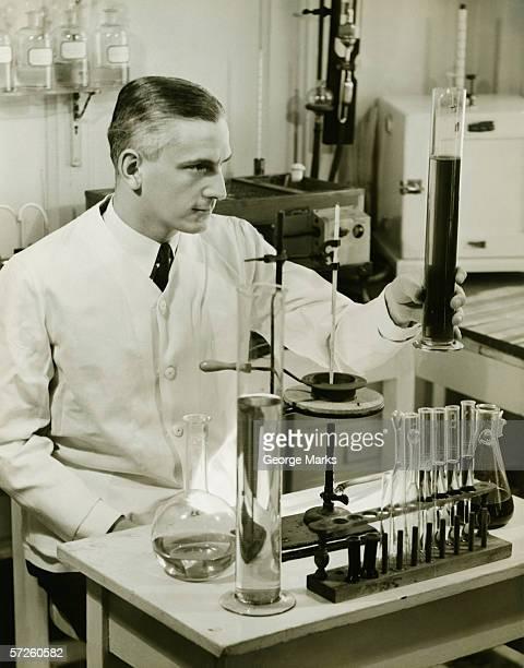 Pharmacien mâle travail avec des tubes à essai laboratoire (B & W