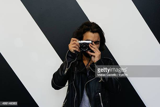 Male photographer against striped wall