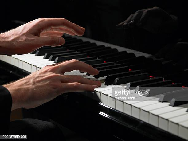 Male pianist playing piano, close-up