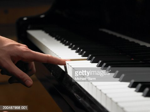 Male pianist pressing single piano key, close-up, side view : Stock Photo