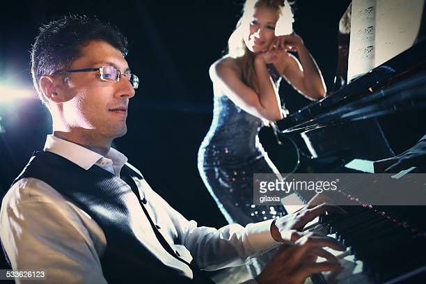Male pianist with female singer waiting for cue.
