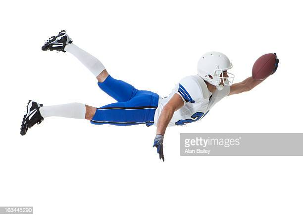 Male player of American football catching ball, studio shot