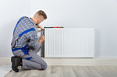 Rear View Of Male Plumber Fixing Thermostat With Screwdriver And Wrench On Radiator