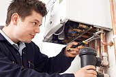 Male Plumber Working On Central Heating Boiler