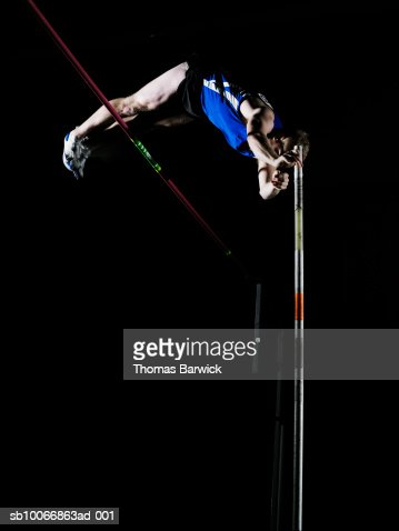 Male pole vaulter clearing bar
