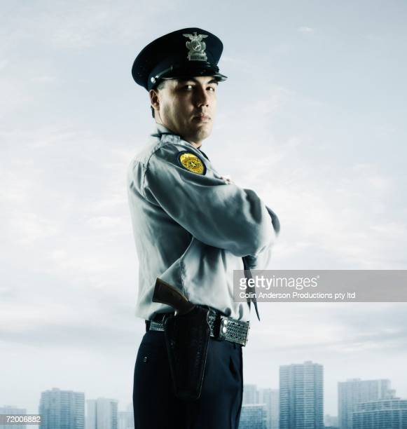 Male police officer in front of cityscape
