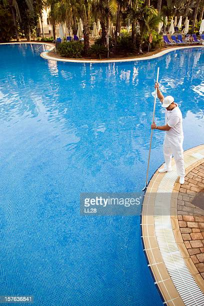 Male pool cleaner cleaning a blue pool