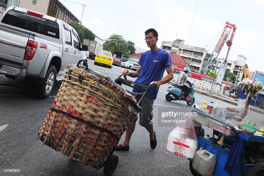 A male porter with a push cart seen on a busy street on October 25, 2012 in Bangkok, Thailand.