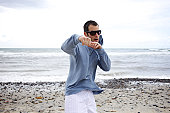 Male pretends he is fighting at the beach.