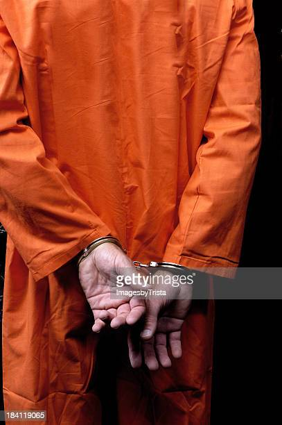 Male prisoner in orange suit his arms handcuffed behind back
