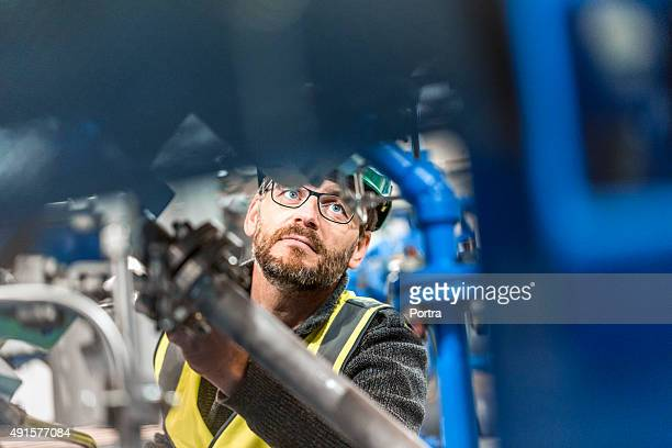 Homme professionnel à l'examen machine de fabrication