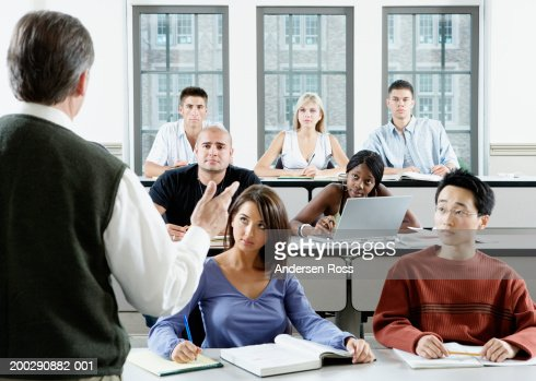 Male professor addressing group of college students in classroom : Stock Photo