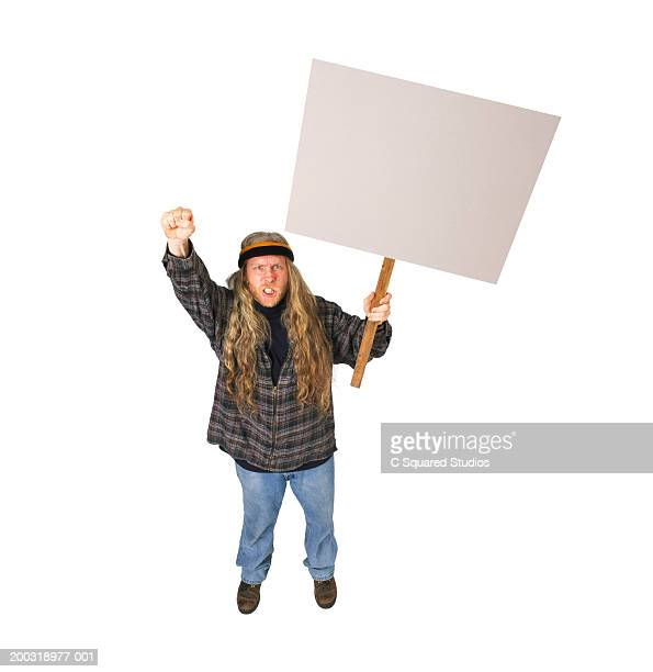 Male protester holding sign, fist in air, clenching teeth, portrait