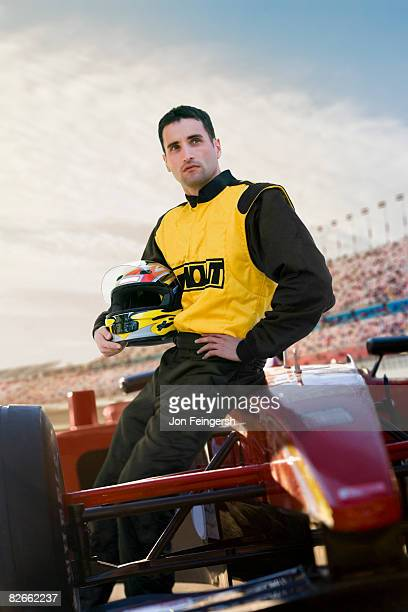 Male Racecar Driver leaning on car