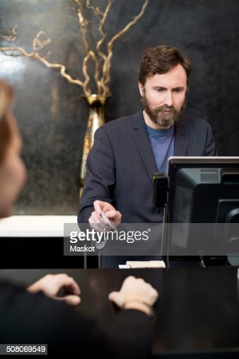 Male receptionist accepting payment through credit card from customer in hotel
