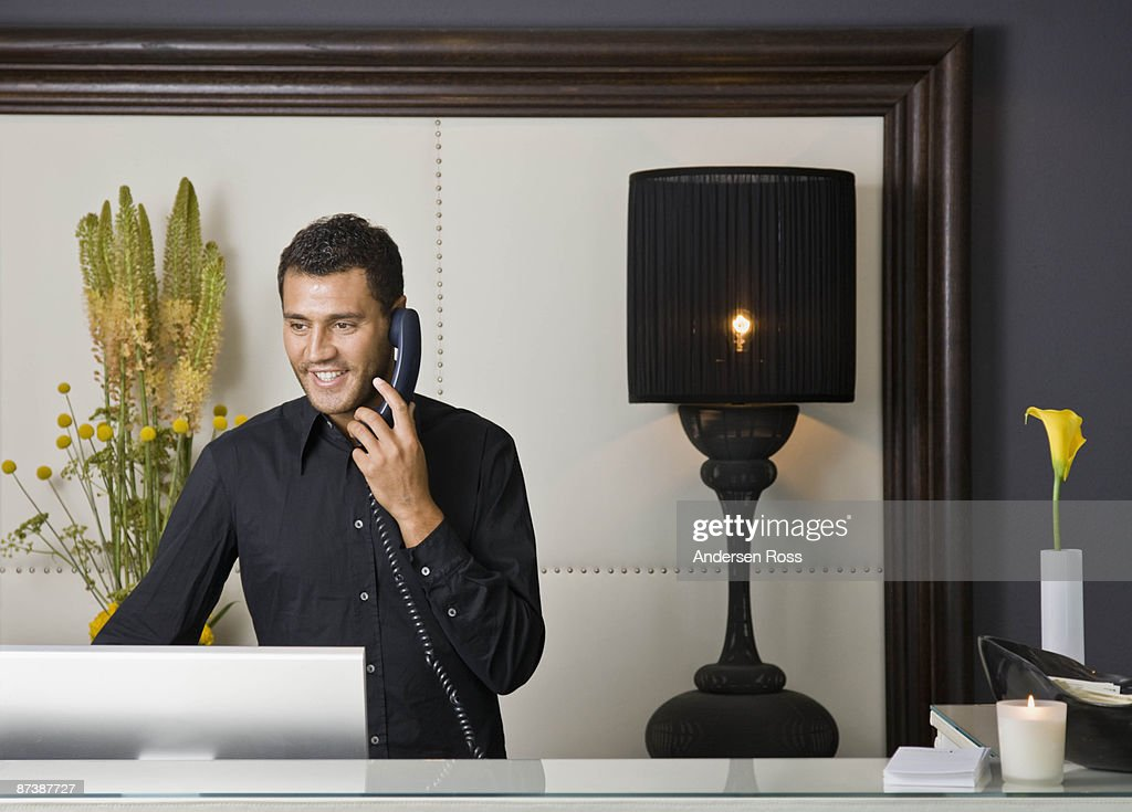 Male receptionist talking on the phone : Stock Photo