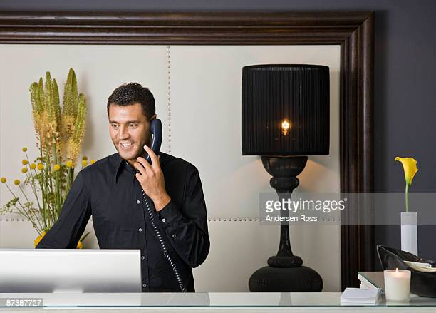 Male receptionist talking on the phone
