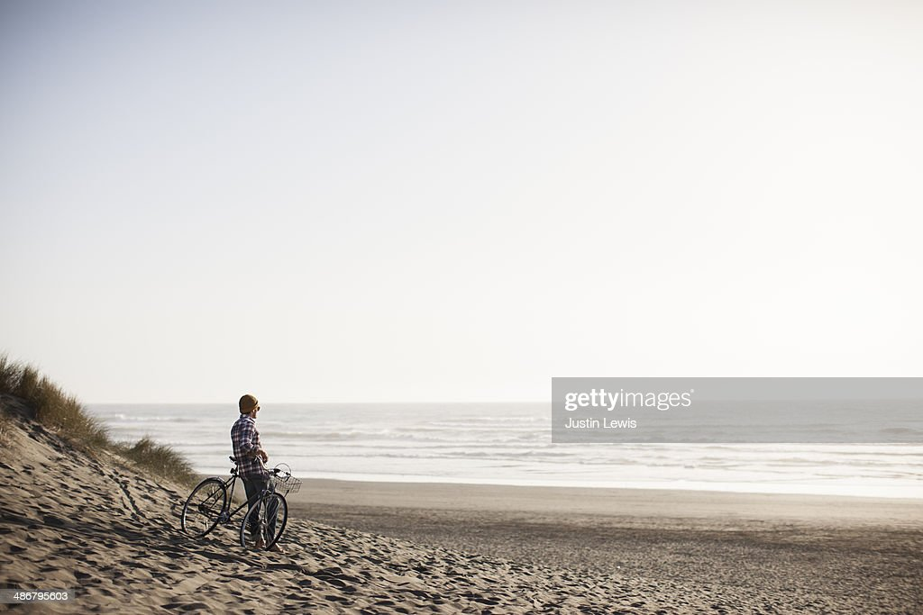 Male resting on bicycle on sandy beach and ocean