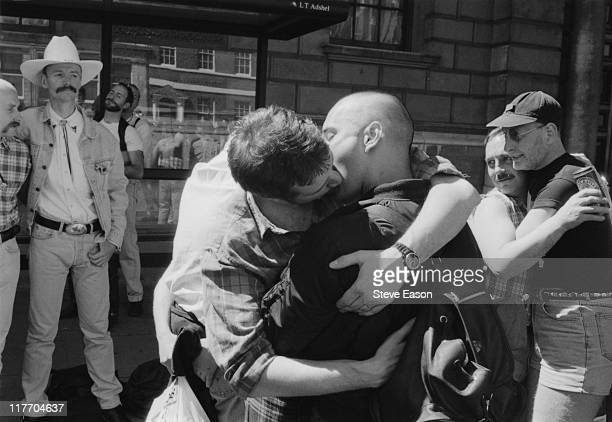 Male revellers hugging and kissing during the Gay Pride parade in London England United Kingdom 6 July 1996