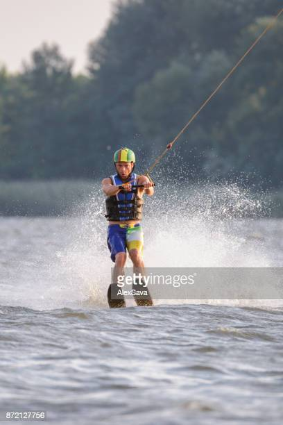 Male riding on lake with water skis