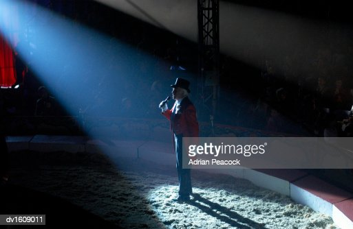 Male Ringmaster Stands in a Spot lit Circus Ring, Making an Announcement to the Audience : Bildbanksbilder