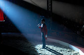 Male Ringmaster Stands in a Spot lit Circus Ring, Making an Announcement to the Audience