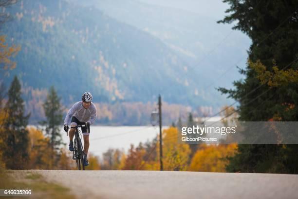 Un coureur cycliste monte jusqu'à une route de campagne tranquille en Colombie-Britannique, Canada à l'automne.