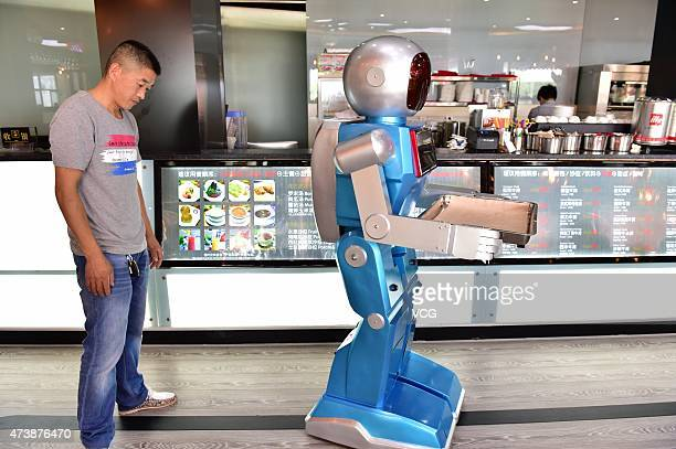 A 'male' robot waiter delivers meals for customers at robotthemed restaurant on May 18 2015 in Yiwu Zhejiang province of China Sophomore Xu Jinjin in...