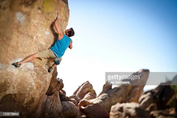 Male rock climber bouldering.