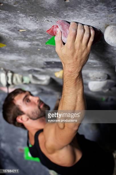 male rock climber climbing gym