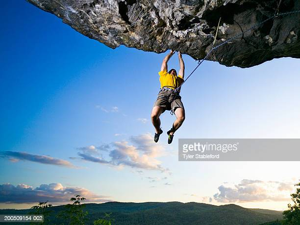 Male rock climber clinging to overhanging rock, low angle view