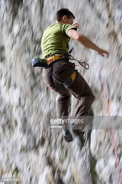 Male rock climber free falling